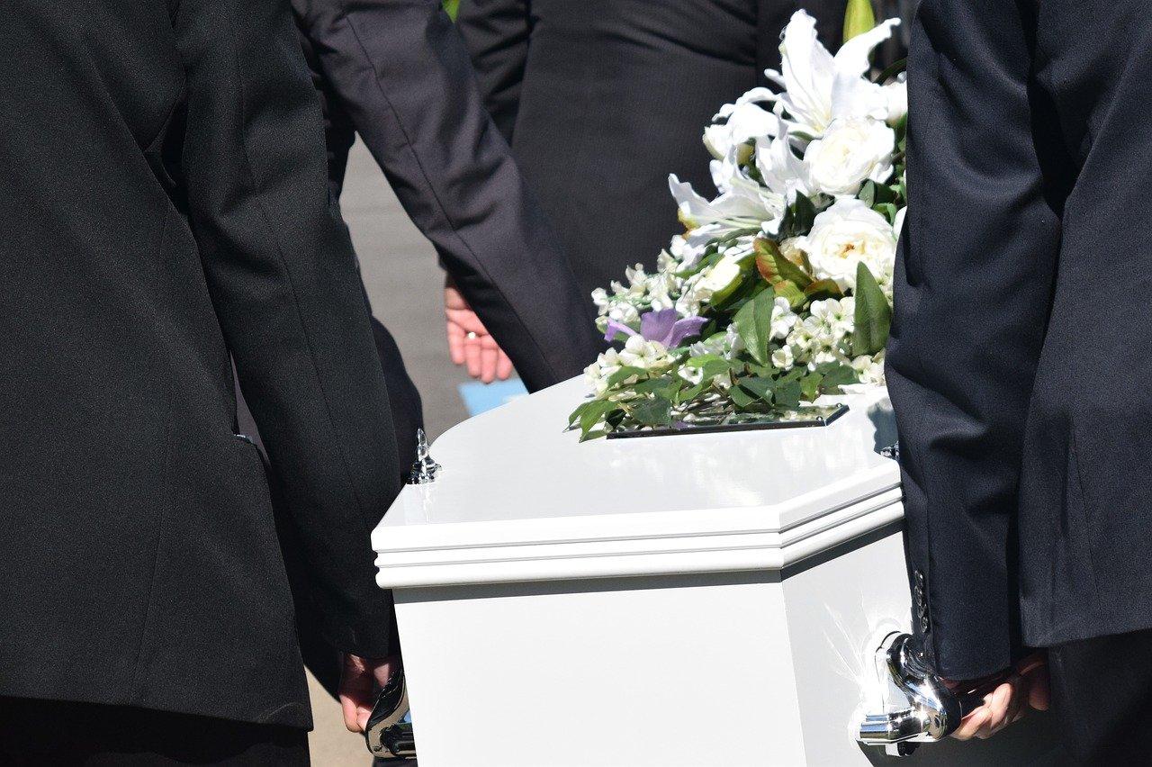 men carrying white casket